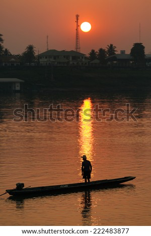 Sunset on Mekong river with man silhouette, on a small wooden boat, Vientiane, Laos - stock photo