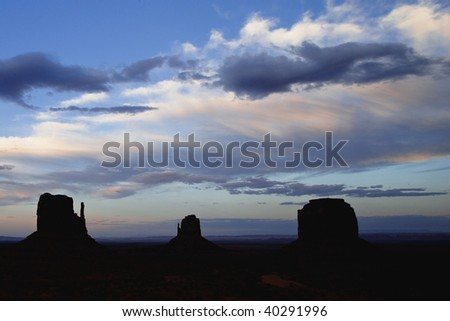 Sunset on Monument Valley Butte Formations better known as the Mittens Monument Valley Navajo Tribal Park Utah Arizona - stock photo