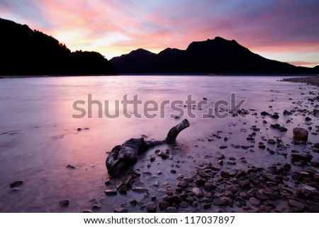 Sunset on mountain lake - stock photo