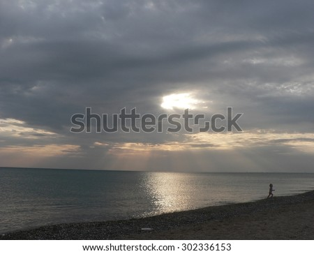 Sunset on sea with grey cloudy sky, running boy, rays of light and beach - stock photo