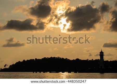 sunset on silhouette little island at pier with lighthouse - stock photo