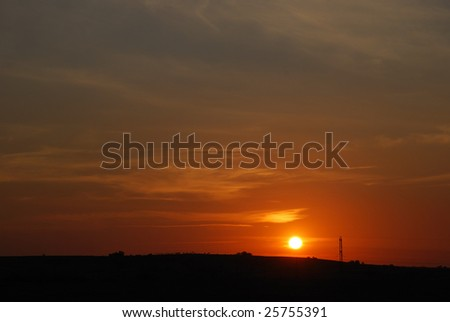 Sunset on summer landscape with electrical pylons and wires - stock photo
