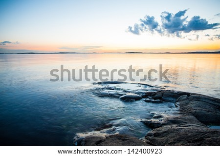 Sunset on swedish coast overlooking the sea - stock photo