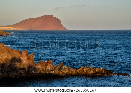 Sunset on the Atlantic Ocean with a Mountain in Background El Medano Tenerife Canary Islands Spain - stock photo