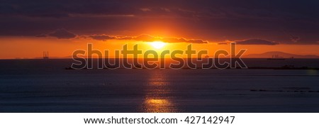 Sunset on the beach. Gold hours becoming blue hours. Landscape, sitting down sun with heaven. - stock photo