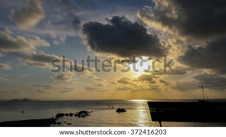 Sunset on the beach next to the calm sea - stock photo
