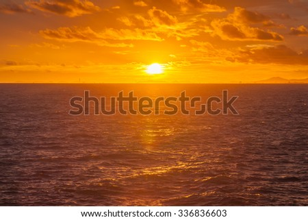 Sunset on the Beach, the sun reflecting off the clouds and sea blue. In the evening at the seaside - stock photo