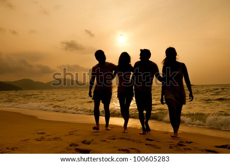Sunset on the beach with friends - stock photo