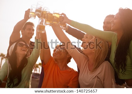 Sunset on the Boardwalk with friends at the beach cheering with Beer at a Bistro - stock photo