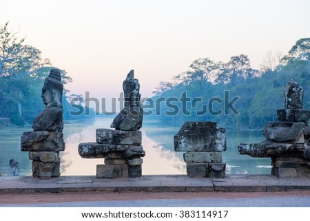 Sunset on the causeway to the South Gate of Angkor Thom with Gods and demons pulling on a giant snake leading to  the city built by King Jayavarman VII 1190-1210 - stock photo