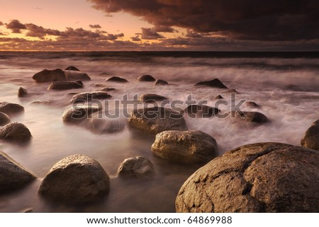 Sunset on the coast of the Baltic Sea. A combination of pictures from water exposures with different shutter speeds: short and long. - stock photo