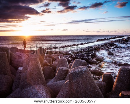 Sunset on the coast of the Riga Gulf at dawn with rocks in foreground - stock photo