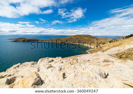 Sunset on the Island of the Sun, Titicaca Lake, among the most scenic travel destination in Bolivia. Glowing rocks in the foreground with snowcapped mountain range (Cordillera real) in the background. - stock photo