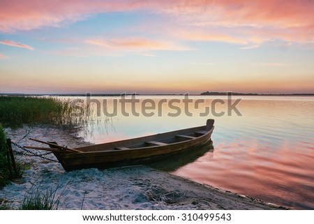 Sunset on the lake, fishing boat on the shore - stock photo