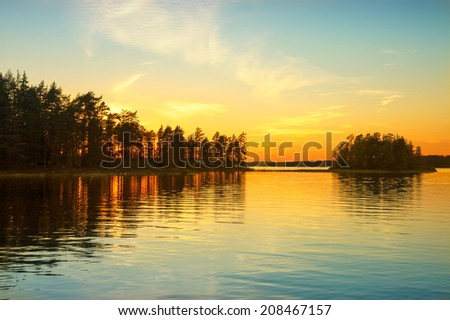 Sunset on the Norwegian lake. Sky reflected on water surface. - stock photo