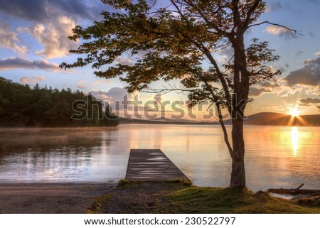 Sunset on the shore of Seventh Lake in the Fulton Chain Lakes region of the Adirondack Mountains of New York - stock photo