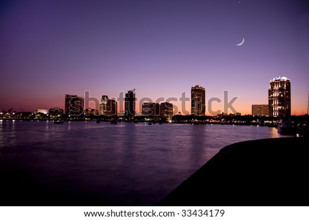 Sunset on the waterfront in St. Petersburg, Florida showing buildings, boats, bay and heron bird in shillouette and cresent moon.  The sky and water shows shades of purple and orange. - stock photo