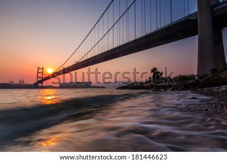 Sunset on Tsing Ma Bridge, Hong Kong. - stock photo