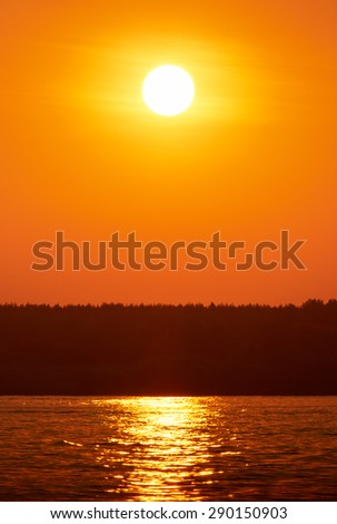 Sunset or sunrise over a river or lake - stock photo