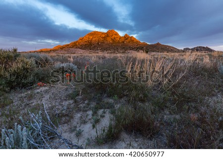 Sunset over a desert peak. This photo was taken near Delta Utah and contains sage brush, mountains, clouds, sunset, dirt, nature, trees, green - stock photo