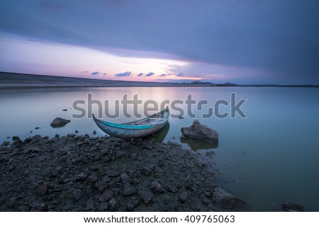 Sunset over a dugout canoe - stock photo