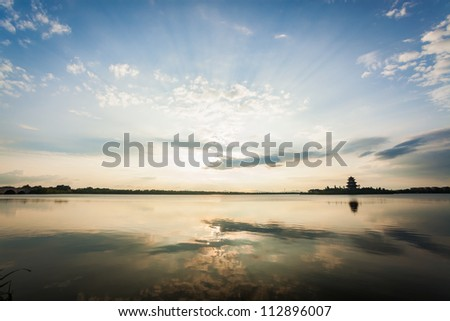 sunset over a lake with ancient chinese tower building - stock photo