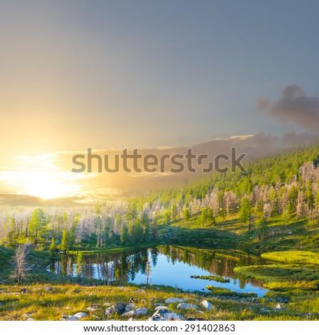 sunset over a mountain lake - stock photo