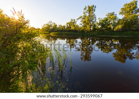 sunset over a quiet river - stock photo