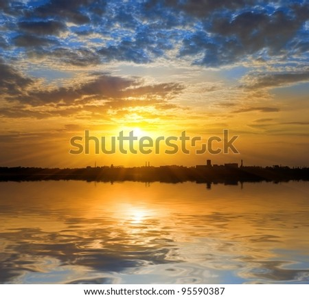 sunset over a town silhouette - stock photo