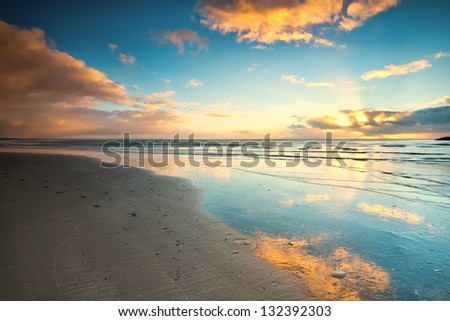 sunset over beach at North sea in Netherlands - stock photo