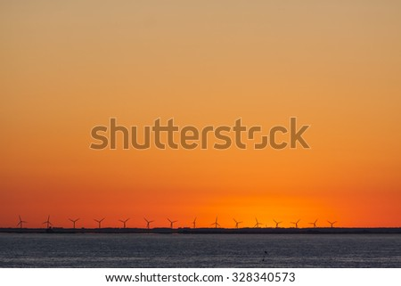 Sunset over Copenhagen Denmark with a offshore wind park in the background and Oresund in the foreground - stock photo