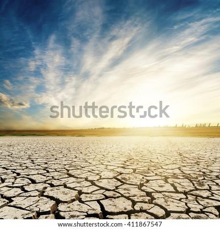 sunset over cracked desert - stock photo