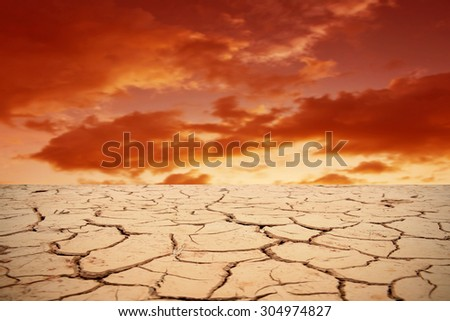 Sunset over cracked earth - stock photo