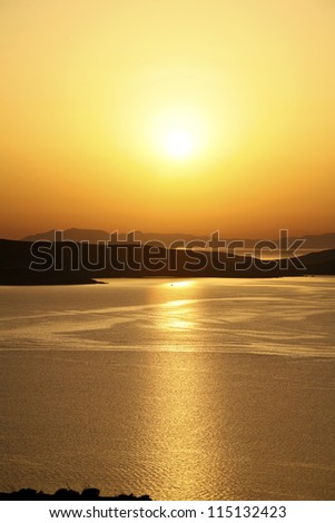 Sunset over Delos Greece A view of the beautiful sunset from Mykonos towards Delos - stock photo