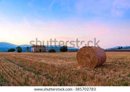 Sunset over farm field with hay bales near Sault, Provence-France - stock photo