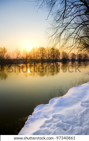 Sunset over frozen river in winter, - stock photo