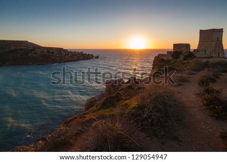 Sunset over Gnejna Bay and Ghajn Tuffieha Tower, Malta - stock photo