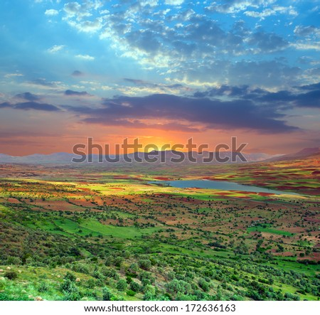 Sunset over green valley - stock photo