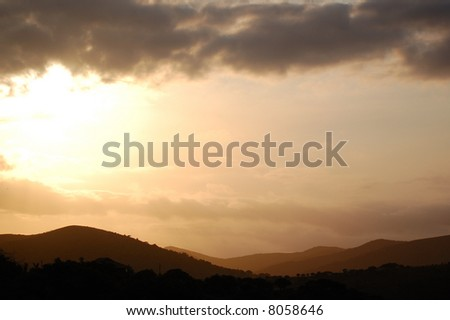 Sunset over hills - stock photo