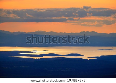 Sunset over Lake Champlain and the Adirondacks of New York from the top of Mt. Mansfield Vermont, USA - stock photo