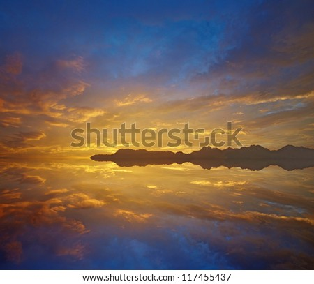 sunset over lake,Dramatic sky with vivid orange and blue cloudscape reflected on the water - stock photo