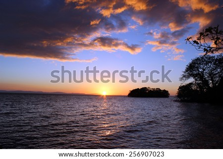 Sunset over Lake Nicaragua with a nearby island - stock photo