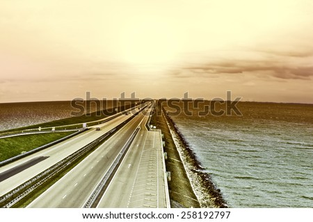 Sunset over Modern Highway on the Protective Dam in Netherlands, Vintage Style Toned Picture - stock photo