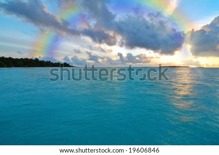 Sunset over ocean and a rainbow in the sky - stock photo