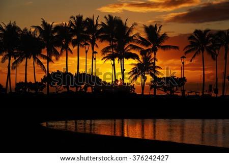 sunset over palm trees and Lagoon beach from Waikiki Beach, Honolulu, Oahu, Hawaii - stock photo
