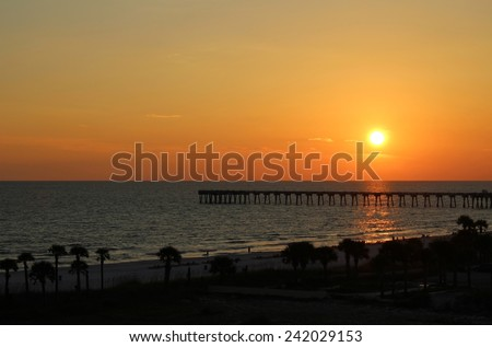 Sunset over pier - stock photo