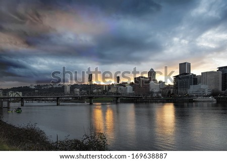 Sunset Over Portland Oregon Downtown Along Willamette River with Sun Rays and Clouds Between Hawthorne Bridge - stock photo