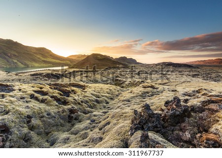 Sunset over Reykjanes peninsula, close to Reykjavik in Iceland, moss grown lava covering the landscape with mountains and a small lake in the background - stock photo