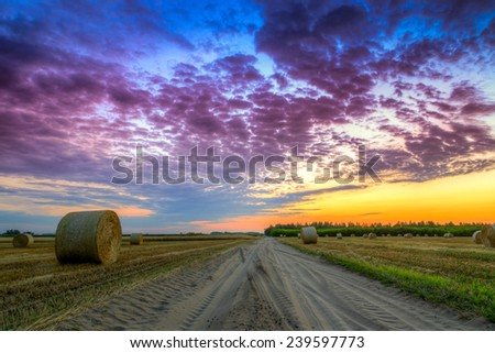 Sunset over rural road and farm field with hay bales-This photo make HDR - stock photo