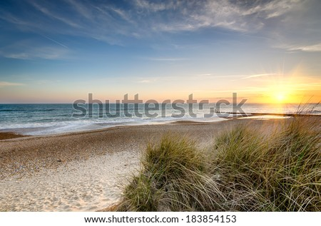 Sunset over sand dunes at Hengistbury Head beach near Bournemouth in Dorset - stock photo